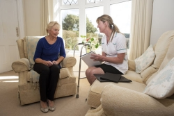 caregiver on a home visit talking with an elderly female patient
